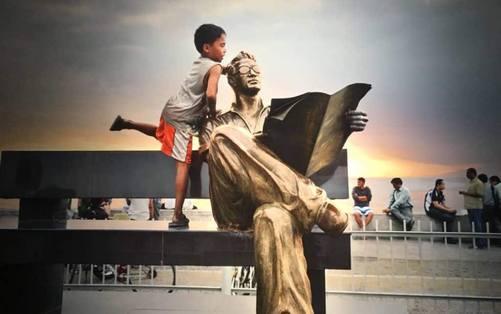 Bambino con statua che legge di Steve McCurry